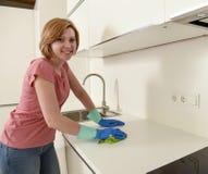 Mujer que sonríe lavado y limpieza felices y positivos con el paño una cocina moderna Foto de archivo