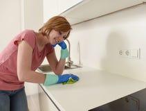 Mujer que sonríe lavado y limpieza felices y positivos con el paño una cocina moderna Fotografía de archivo