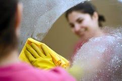 Mujer que sonríe limpiando un espejo Fotos de archivo libres de regalías
