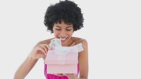 Mujer que sonríe mientras que ella abre una caja de regalo almacen de video