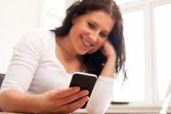 Mujer que sonríe mientras que lee el mensaje de texto Imagenes de archivo