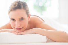 Mujer que sonríe mientras que se relaja en balneario de la salud Imagenes de archivo