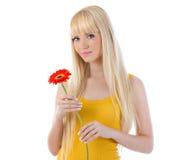 Mujer que sonríe mientras que sostiene la flor Fotografía de archivo