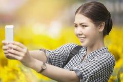 Mujer que sonríe mientras que toma la imagen del selfie con el teléfono móvil en s foto de archivo