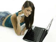 Mujer que sonríe mostrando el de la tarjeta de crédito Imágenes de archivo libres de regalías