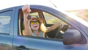 Mujer que sonríe mostrando nuevas llaves del coche almacen de metraje de vídeo