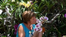 Mujer que sonríe, oliendo y admirando las orquídeas coloridas almacen de metraje de vídeo