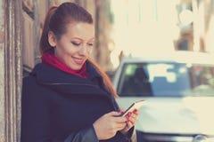 Mujer que sonríe sosteniendo un teléfono móvil que se coloca al aire libre al lado del nuevo coche imágenes de archivo libres de regalías