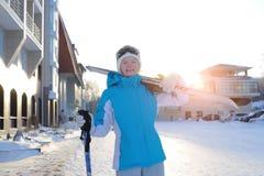 Mujer que sonríe y que celebra el esquí La estación de esquí Foto de archivo