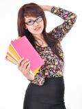 Mujer que sonríe y que presenta los libros que llevan Fotografía de archivo