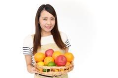 Mujer que sonr?e con las frutas foto de archivo