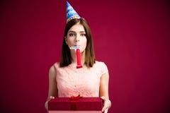 Mujer que sopla en silbido y que sostiene la caja de regalo Fotografía de archivo libre de regalías