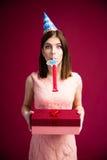 Mujer que sopla en silbido y que sostiene la caja de regalo Imágenes de archivo libres de regalías