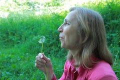 Mujer que sopla en un diente de león Fotografía de archivo libre de regalías
