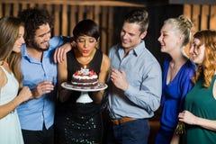 Mujer que sopla la vela en su torta de cumpleaños Imagen de archivo libre de regalías