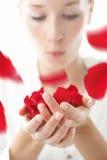 Mujer que sopla los pétalos color de rosa rojos Fotografía de archivo