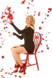 Mujer que sopla sentarse color de rosa de los pedales imagenes de archivo