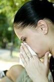 Mujer que sopla su nariz Fotos de archivo
