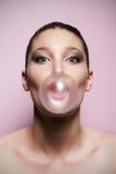 Mujer que sopla una burbuja grande del chicle Foto de archivo libre de regalías