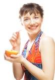 Mujer que sorbe el zumo de naranja con una paja Imagenes de archivo