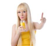 Mujer que sorbe el zumo de naranja y que da los pulgares para arriba Imágenes de archivo libres de regalías