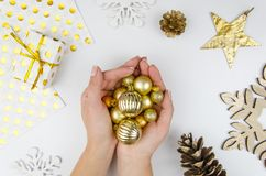 Mujer que sostiene bolas de oro de la Navidad Endecha plana, visión superior Fotos de archivo libres de regalías