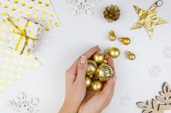 Mujer que sostiene bolas de oro de la Navidad Muchacha que se prepara por días de fiesta, adornando para el árbol de navidad Ende Imagen de archivo libre de regalías
