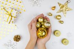 Mujer que sostiene bolas de oro de la Navidad Muchacha que se prepara por días de fiesta, adornando para el árbol de navidad Fond Fotos de archivo