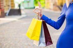 Mujer que sostiene bolsos de compras Shopaholic al aire libre Imagenes de archivo