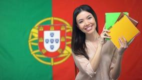 Mujer que sostiene cuadernos contra el fondo portugués de la bandera, aprendiendo lengua almacen de metraje de vídeo