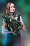 Mujer que sostiene el árbol de los christmass Imagenes de archivo