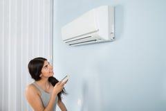 Mujer que sostiene el acondicionador de aire teledirigido Imagen de archivo