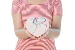 Mujer que sostiene el aislante del buey del regalo del corazón en el fondo blanco Fotografía de archivo libre de regalías