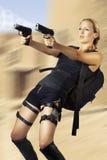 Mujer que sostiene el arma de dos manos Fotografía de archivo