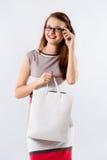 Mujer que sostiene el bolso blanco que hace compras Foto de archivo libre de regalías
