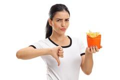 Mujer que sostiene el bolso de fritadas y que da el pulgar abajo Imagenes de archivo