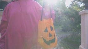 Mujer que sostiene el bolso del truco o de la invitación, pidiendo dulces en la entrada del partido de Halloween almacen de metraje de vídeo