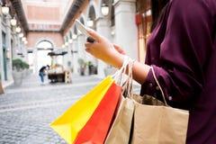 Mujer que sostiene el bolso que hace compras y que usa el smartphone para hacer compras concepto en l?nea, que hace compras imágenes de archivo libres de regalías