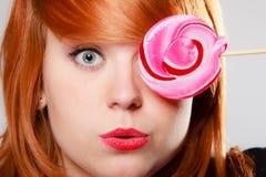 Mujer que sostiene el caramelo. Muchacha de Redhair con la piruleta dulce que se ríe Foto de archivo