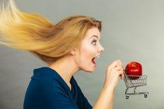 Mujer que sostiene el carro de la compra con la manzana dentro Foto de archivo libre de regalías