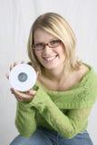 Mujer que sostiene el CD en blanco Foto de archivo libre de regalías
