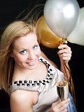 Mujer que sostiene el champán y los globos del Año Nuevo Fotografía de archivo