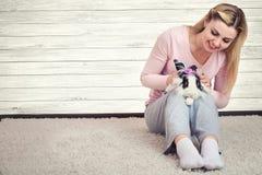 Mujer que sostiene el conejo mullido lindo Animales domésticos preciosos foto de archivo libre de regalías