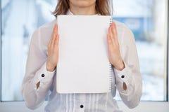 Mujer que sostiene el cuaderno en blanco del anillo-límite Foto de archivo