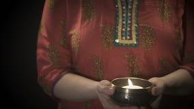 Mujer que sostiene el cuenco tibetian del canto con la vela almacen de metraje de vídeo