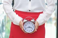 Mujer que sostiene el despertador con la falda roja - mujer en su período Fotografía de archivo libre de regalías