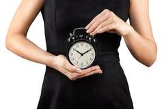 Mujer que sostiene el despertador en las manos, aisladas en blanco Imagenes de archivo