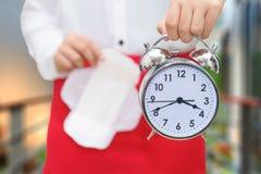 Mujer que sostiene el despertador y la servilleta sanitaria con la falda roja - w Imagenes de archivo