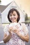 Mujer que sostiene el dinero del efectivo con el fondo de la casa fotos de archivo