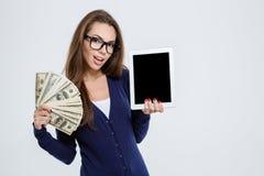 Mujer que sostiene el dinero y que muestra la pantalla de tableta Imágenes de archivo libres de regalías